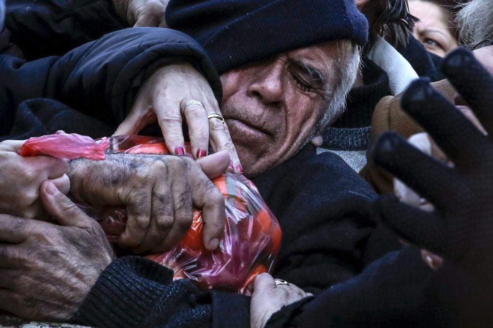 Mężczyzna podczas rozdania produktów rolnych w Atenach