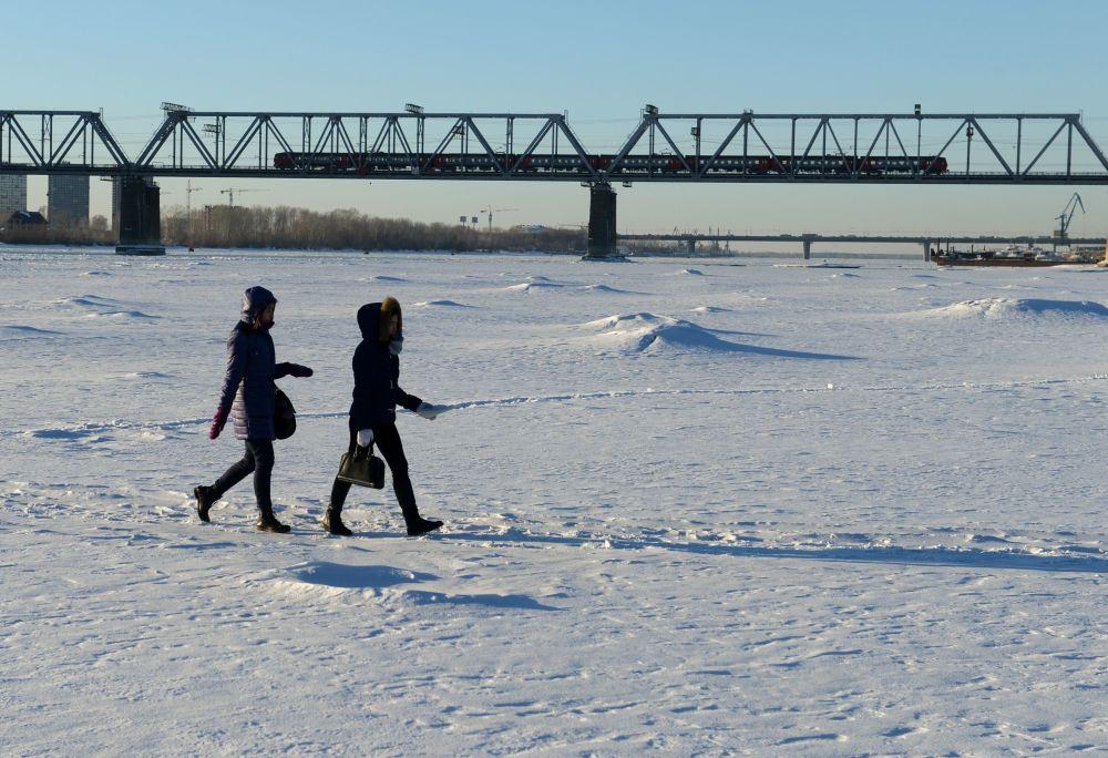 Mieszkańcy Nowosybirska spacerujący po zamarzniętej rzece Ob w pobliżu mostu kolejowego będącego częścią Kolei Transsyberyjskiej.