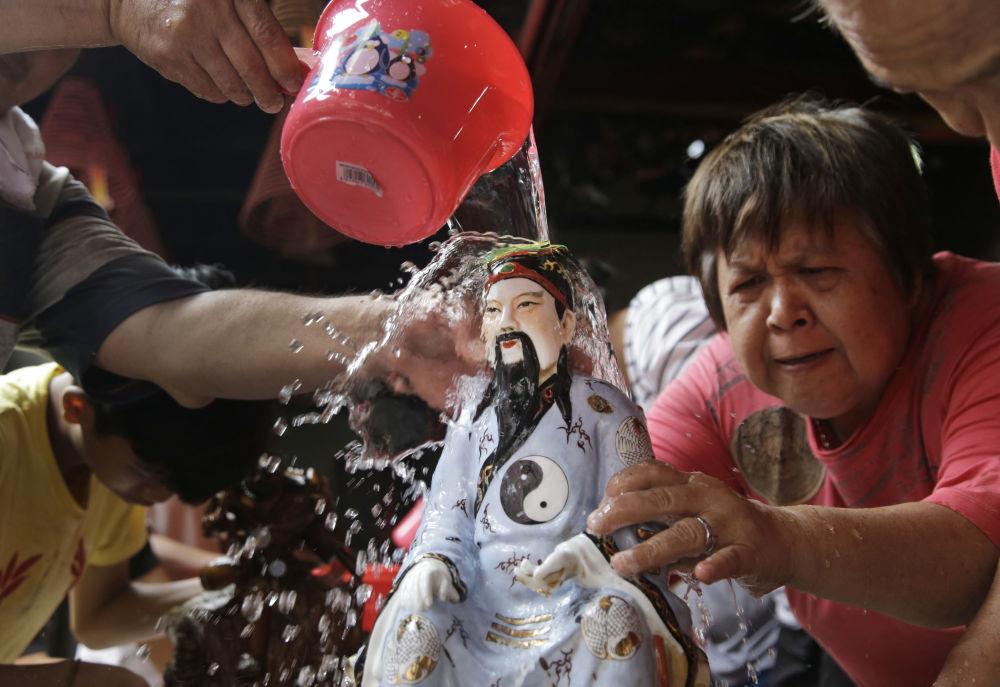 Ludzie myją figurkę chińskiego bóstwa w Indonezji
