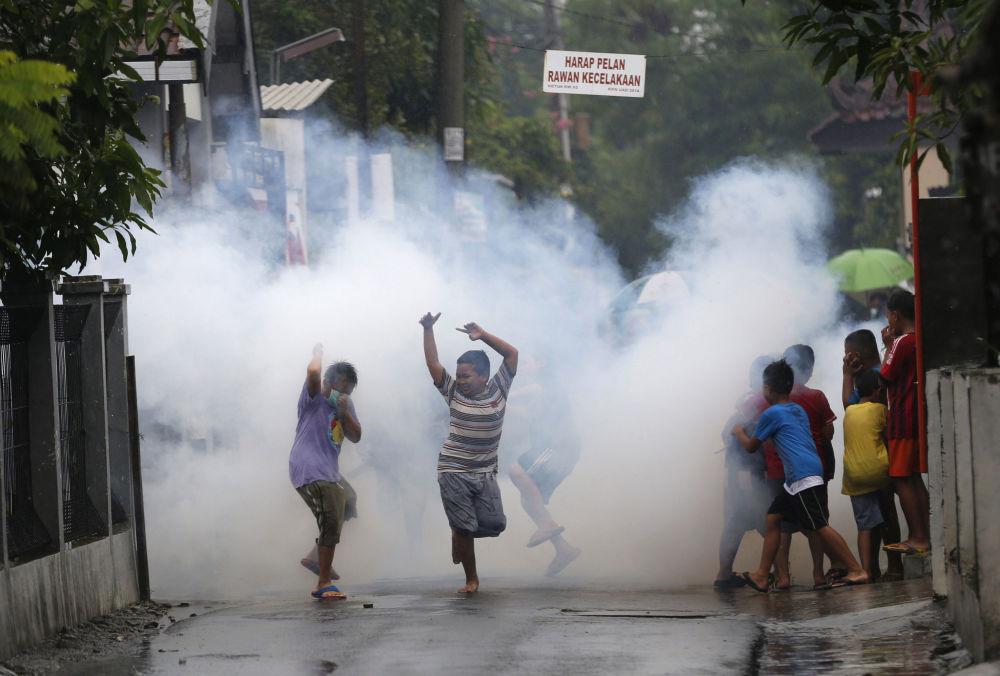 Dzieci w chmurach środków chemicznych, stosowanych do walki z moskitami, Indonezja