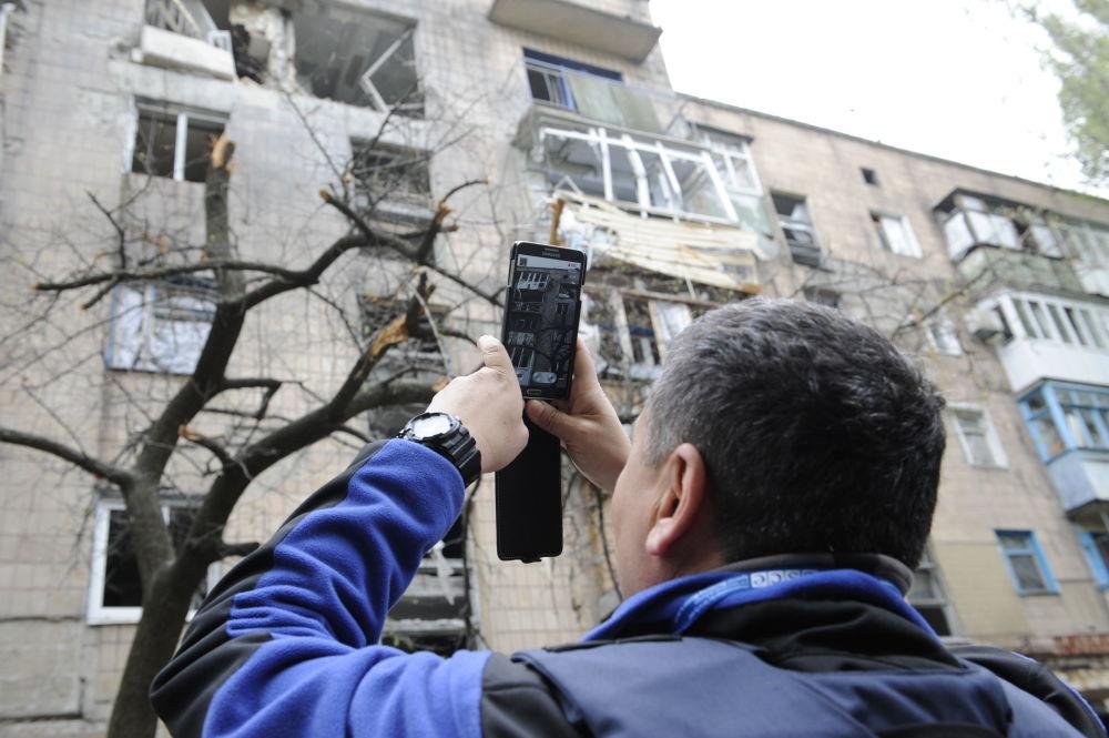 Pracownik misji OBWE ogląda dom, uszkodzony w wyniku ostrzału Doniecka