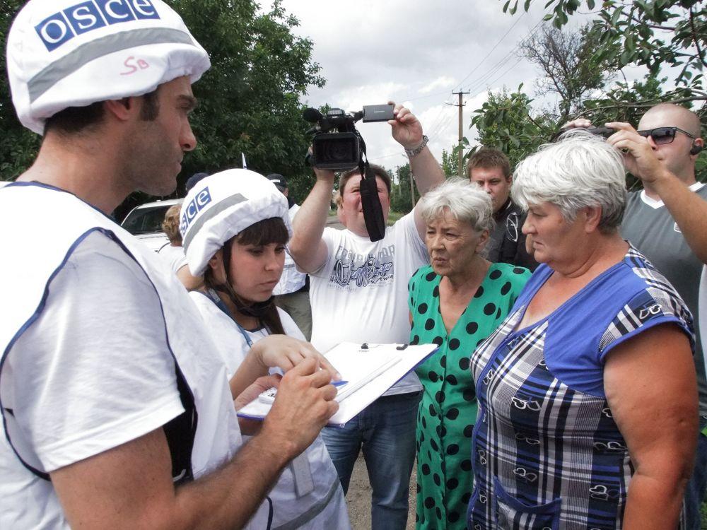 Pracownicy OBWE wypytują mieszkańców wioski Sachanka w obwodzie donieckim, która została obstrzelana przez ukraińskie wojska