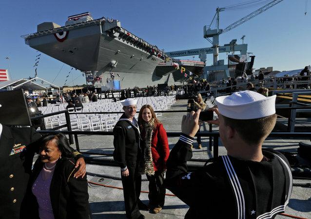 Pozujący na tle USS Gerald R. Ford