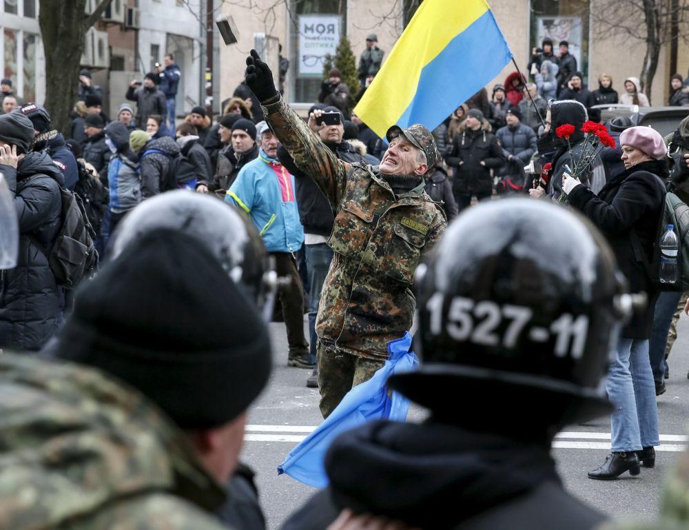 Uczestnik akcji protestacyjnej rzuca kamień w stronę jednego z rosyjskich banków w Kijowie
