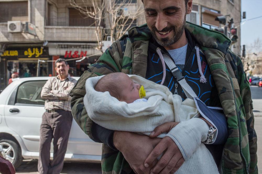 Mężczyzna z dzieckiem na ulicy Damaszku