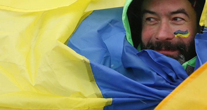 Mężczyzna owinięty we flagę Ukrainy