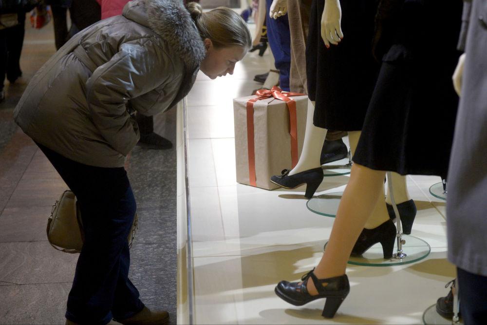 Klientka rozgląda obuwie na manekinach w Domu Handlowym GUM