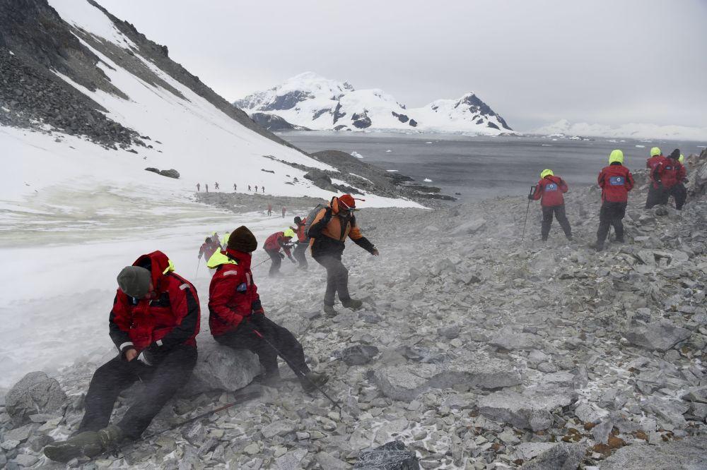 Turyści wspinają się na górę, na Antarktydzie