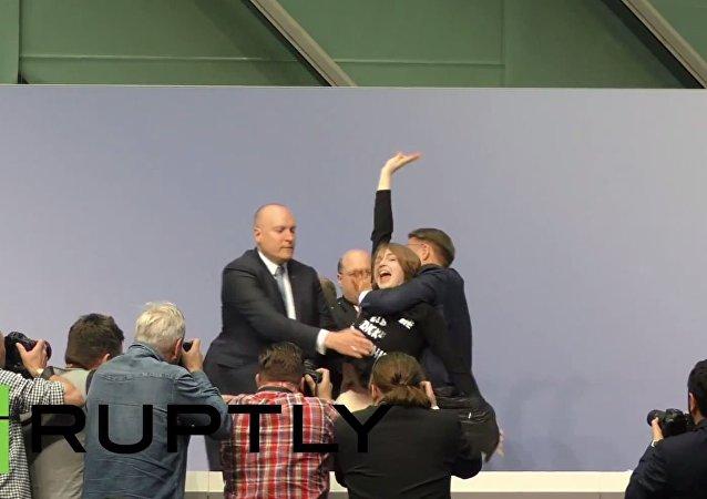 Dziewczyna weszła na biurko szefa EBC, krzycząc Koniec z dyktaturą EBC!