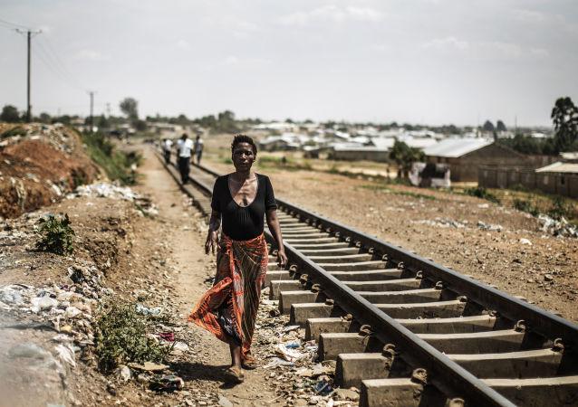 Zambijska kobieta idzie wzdłuż torów