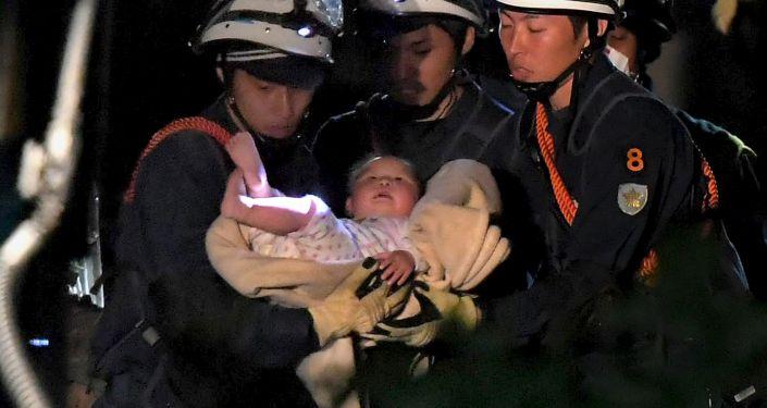 Ratownicy wynoszą dziecka spod ruin po trzęsieniu ziemi w japońskim Kumamoto