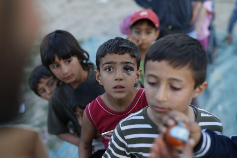 Dzieci imigrantów w kolejce po zabawki w greckim obozie uchodźców