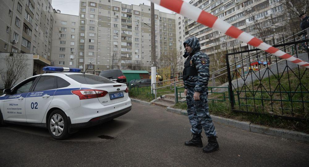 Pracownik organów porządkowych przy moskiewskim bloku, w którym znaleziono skład amunicji i broni