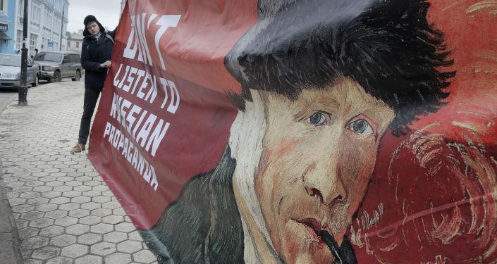 Kijowski aktywista z plakatem Nie słuchajcie rosyjskiej propagandy