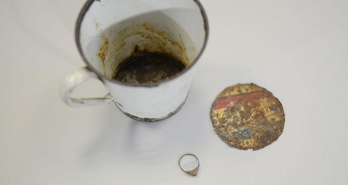 Kubek z podwójnym dnem i pierścionek znalezione w Muzeum Auschwitz