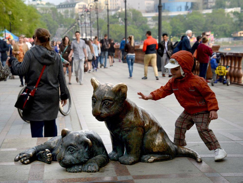 """Dziecko przy rzeźbiarskiej kompozycji """"Tigrita"""" na promenadzie """"Sportiwnaja"""" we Władywostoku."""