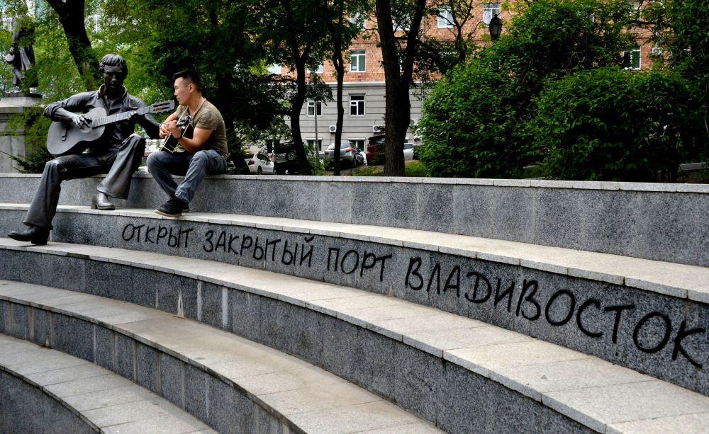 Mężczyzna gra na gitarze przy pomniku Władimira Wysockiego na skwerze Teatralnym we Władywostoku.