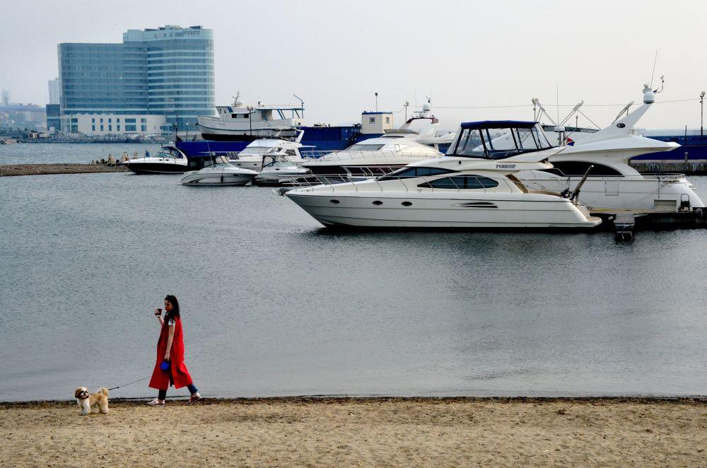 """Dziewczynka z pieskiem na plaży, na tle jachtów w porcie """"Sportiwnyj"""" we Władywostoku."""