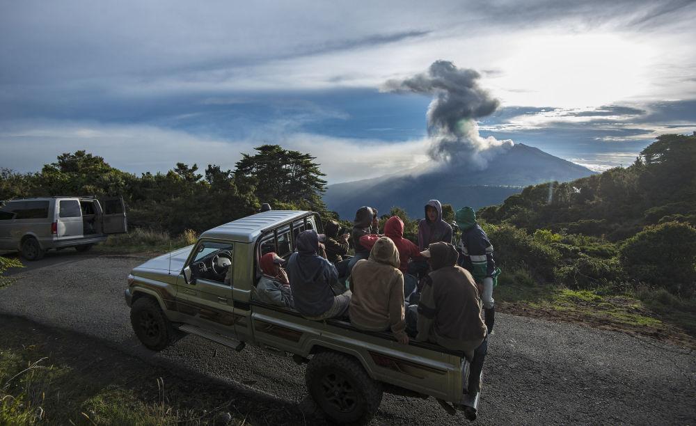 Farmerzy z Kostaryki, siedzący w przyczepie ciężarówki, obserwują aktywność wulkanu.