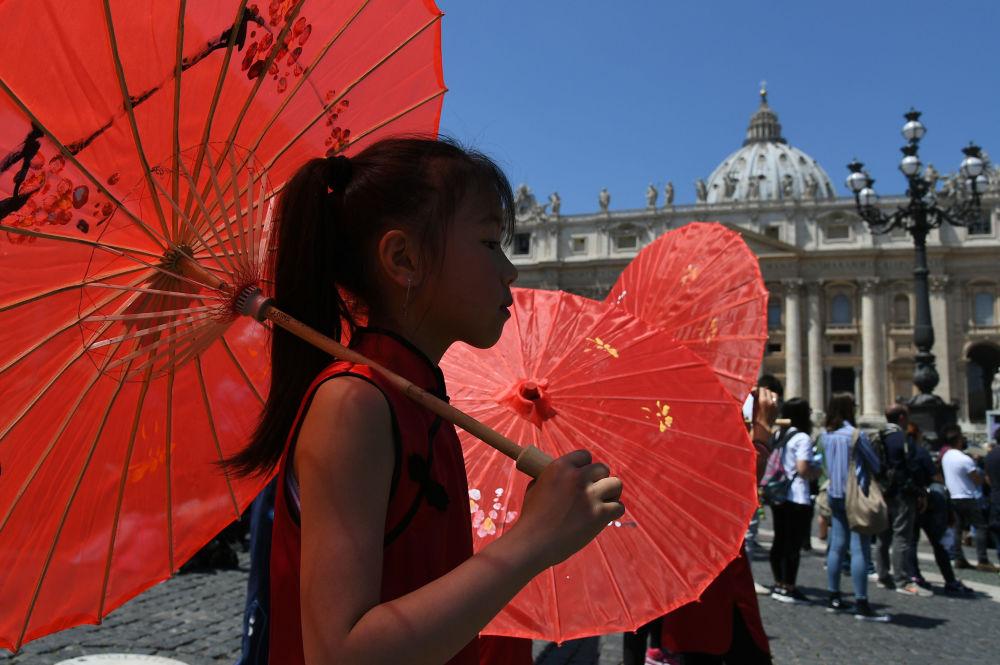 Dziewczynka z czerwoną parasolką przechodzi obok rezydencji Papieża Rzymu w Watykanie.