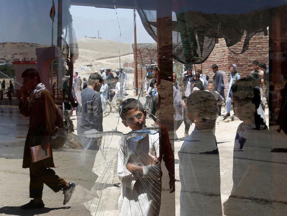 Afgańscy chłopcy przy rozbitym oknie (Kabul, Afganistan).