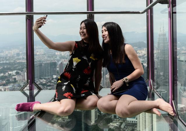 Dziewczyny z Malezji robią sobie zdjęcia w szklanym pomieszczeniu Sky Box na tle panoramicznego widoku z wieży telewizyjnej Manara Kuala Lumpur.