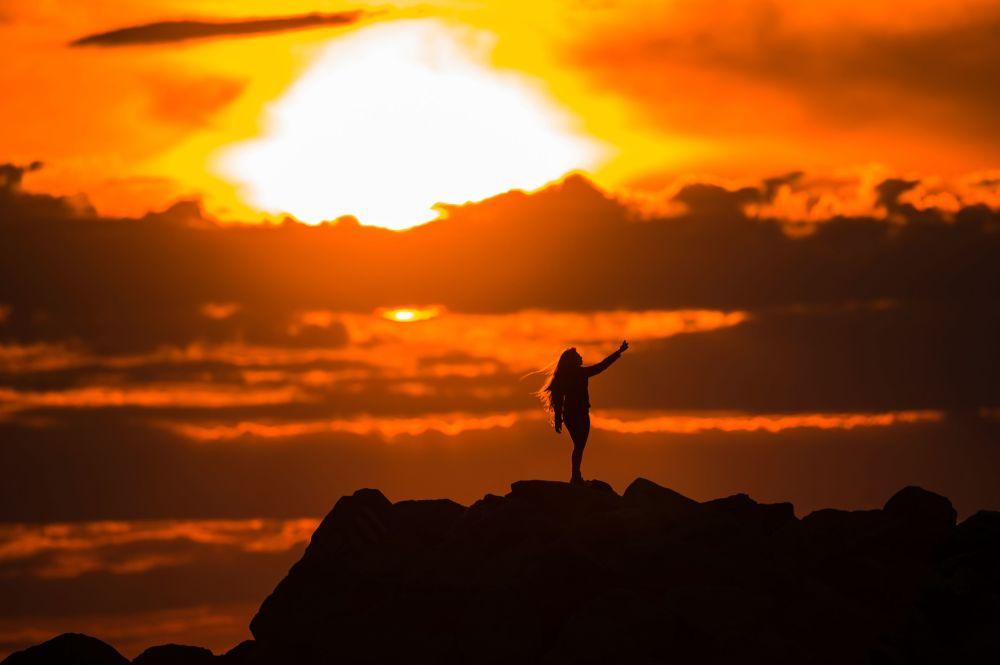 Dziewczyna robi sobie zdjęcie na promenadzie Olimpijskaja w Adlerze (Soczi) na tle zachodzącego słońca.