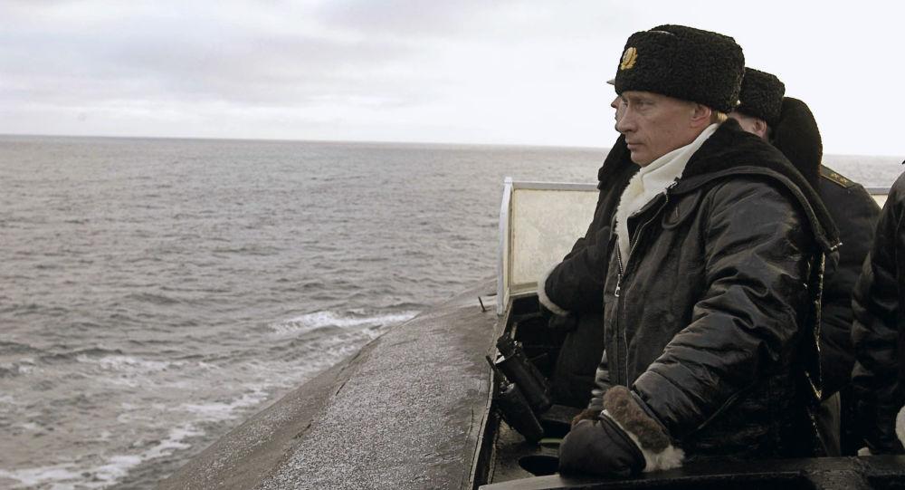 """Prezydent Rosji Władimir Putin obserwuje przebieg manewrów Floty Północnej w pokładu ciężkiego rakietowego krążownika podwodnego o znaczeniu strategicznym """"Archangielsk""""."""