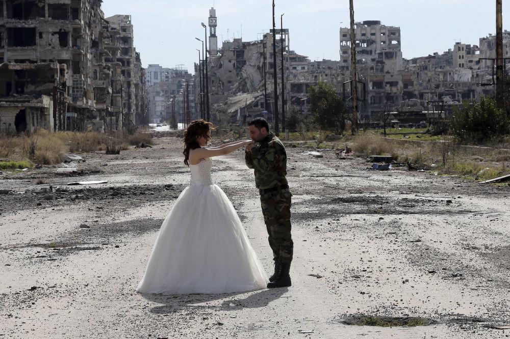 Syryjska para młoda na tle zniszczonego miasta Homs.