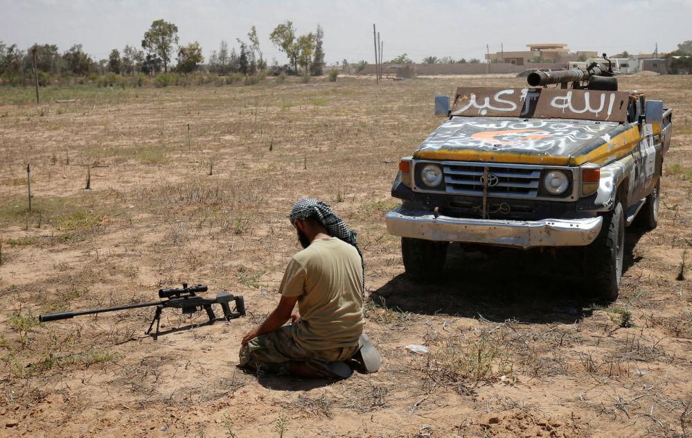 Wojujący o odzyskanie Syrty podczas modlitwy na polu walki.