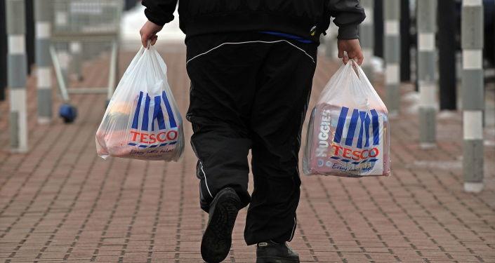 Mężczyzna z zakupami z supermarketu Tesco