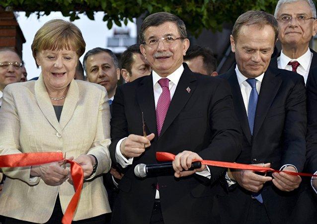 Kanclerz Niemiec Angela Merkel, pemier Turcji Ahmet Davutoglu i przewodniczący Rady Europejskiej Donald Tusk podczas ceremonii przecięcia wstęgi przy Centrum Pomocy Dzieciom w obozie dla uchodźców niedaleko Gaziantep, Turcja, 23 kwietnia 2016