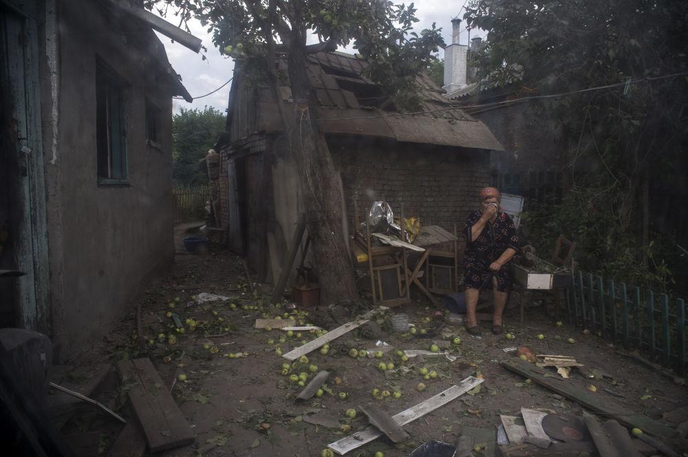 Mieszkanka Ługanska przed domem zniszczonym przez ostrzał artyleryjski miasta dokonany przez wojska ukraińskie