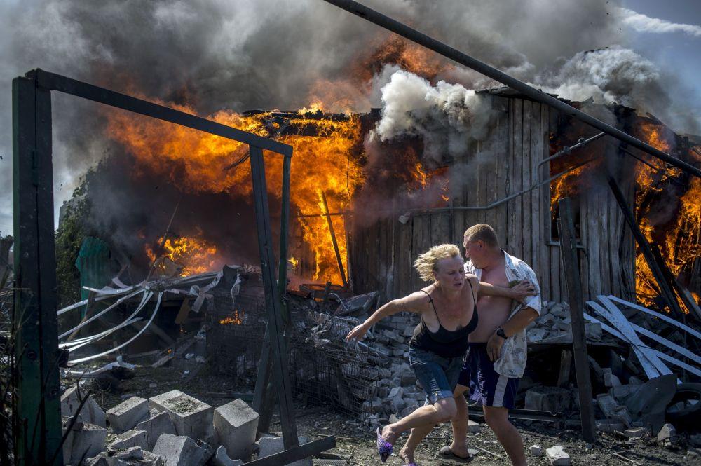Miejscowi mieszkańcy ratują się przed pożarem w obwodzie ługańskim