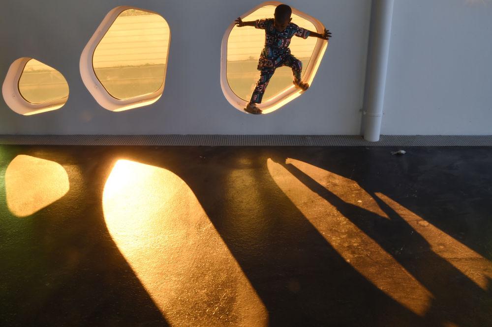 Chłopiec w ramie okiennej na tle zachodzącego słońca we Francji