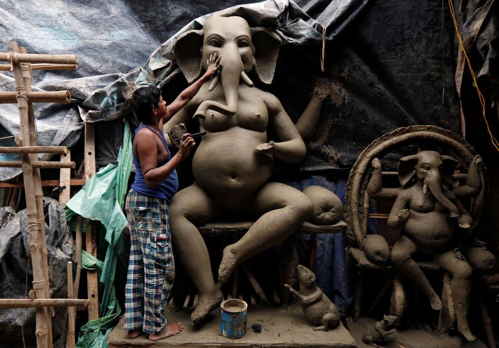 Artysta podczas tworzenia figury hinduistycznego boga Ganeszy, Kalkuta, Indie