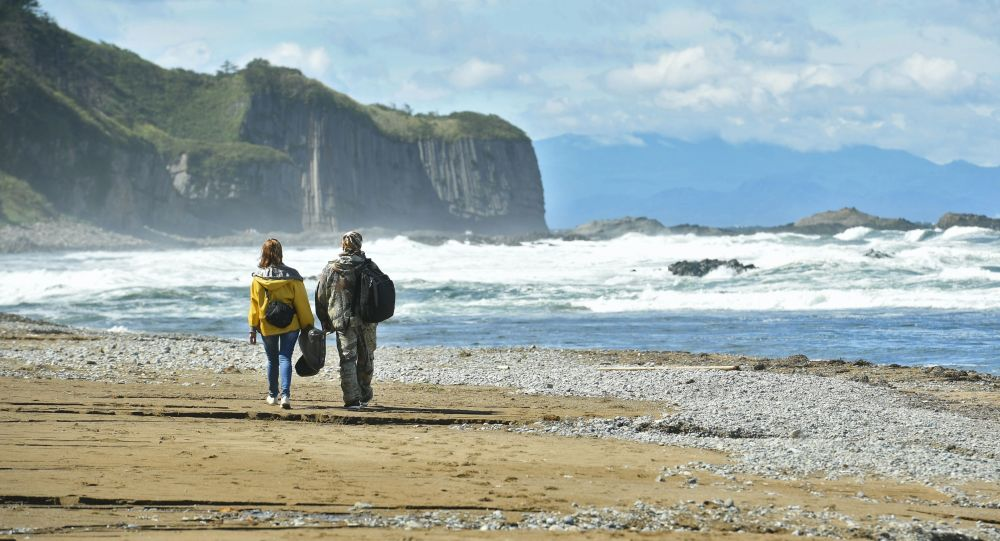 Turyści na brzegu Morza Ochockiego w zachodniej części wyspy Kunaszir.