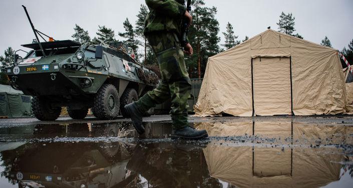 Szwedzki żołnierz na tle transportera opancerzonego Patria XA-360 AMV w bazie wojskowej Nordyckiej Grupy Bojowej w Szwecji