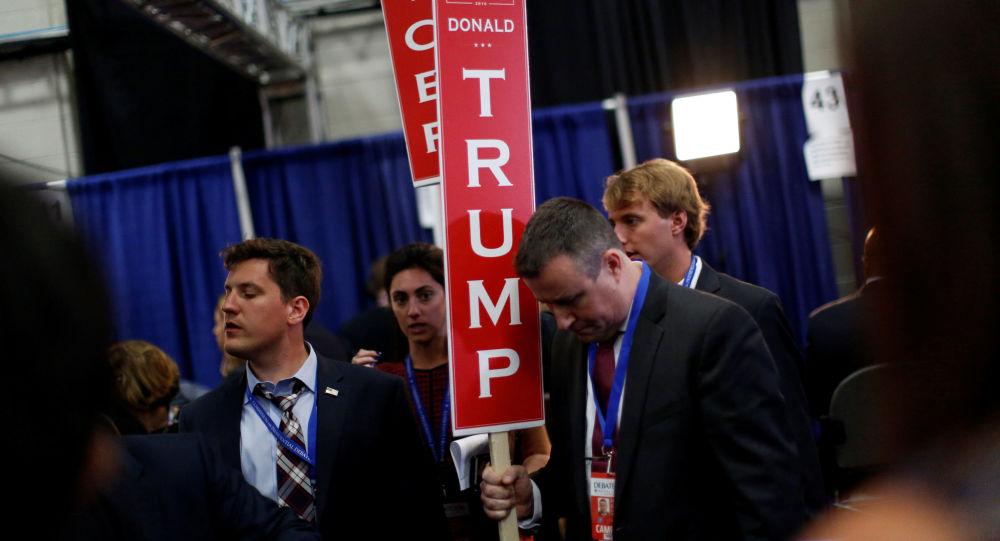 Pracownicy z plakatami po pierwszej debacie kandydatów na prezydenta USA Donalda Trumpa i Hillary Clinton