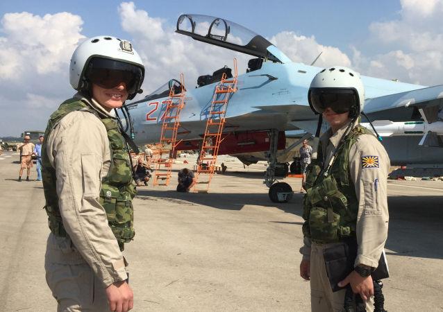 Rosyjscy wojskowi na tle samolotów bojowych Su-30 przed wylotem z bazy Hmeimim w Syrii.