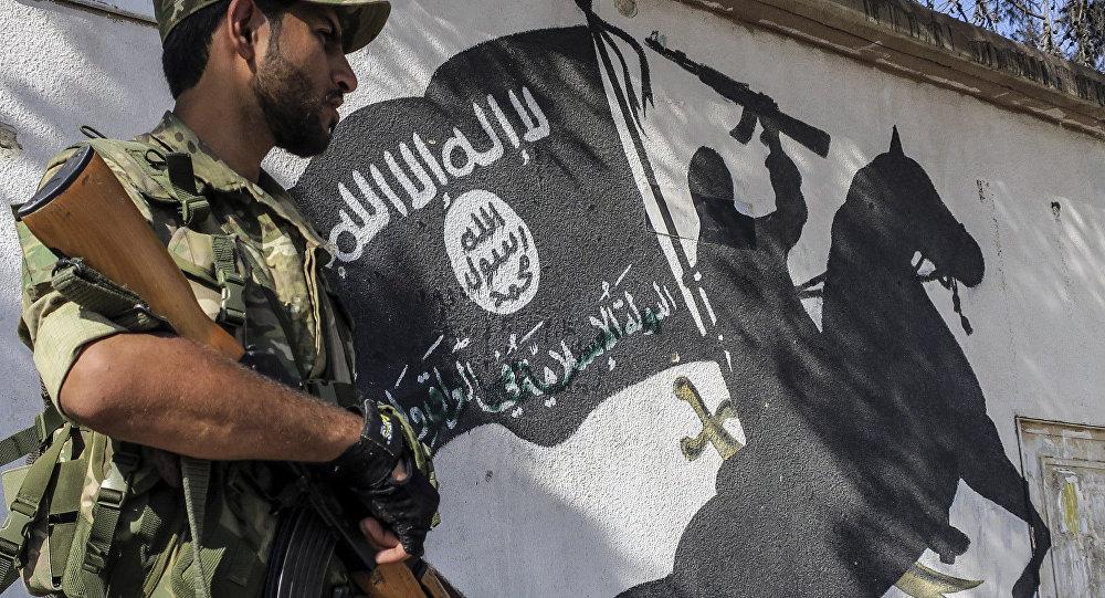 Ein Kämpfer der Freien Syrischen Armee steht vor einem von IS-Milizen an einer Wand hinterlassenen Bild in Jarablus, Syria