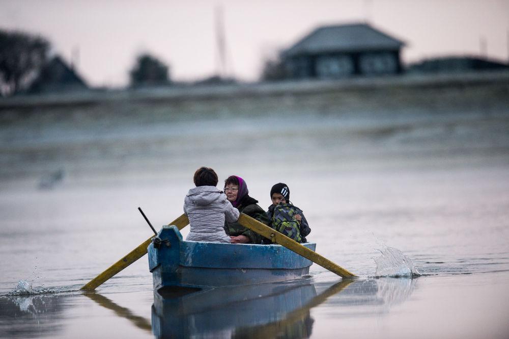 Gulnara Kołdaszewa, matka Ajdara, przewozi syna łodzią na drugi brzeg rzeki Irtysz
