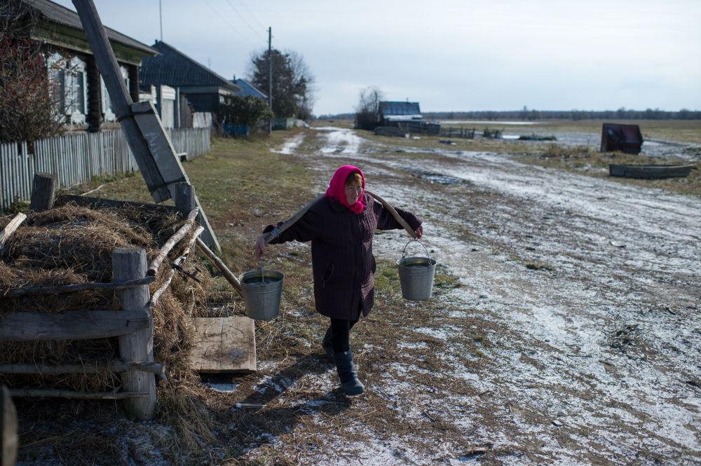 Mieszkanka wsi Sibiliakowo w obwodzie omskim idzie po wodę