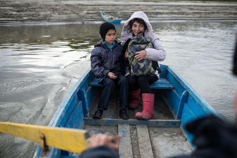 Ajdar Kołdaszew po zajęciach przeprawia się wraz z mamą Gulnarą łodzią przez rzekę Irtysz do domu
