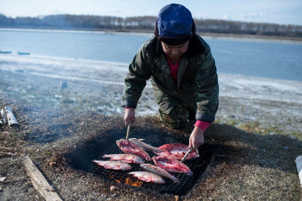 Ojciec Ajdara Kołdaszewa Hanid wędzi rybę, którą pojmał wraz z synem