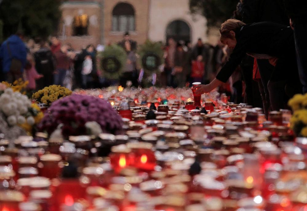 Kobieta zapala świecę na cmenatrzu w Dzień Wszystkich Świętych w Zagrzebie