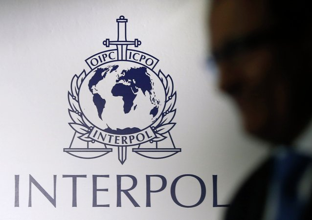A man passes an Interpol logo during the handing over ceremony of the new premises for Interpol's Global Complex for Innovation, a research and development facility, in Singapore September 30, 2014