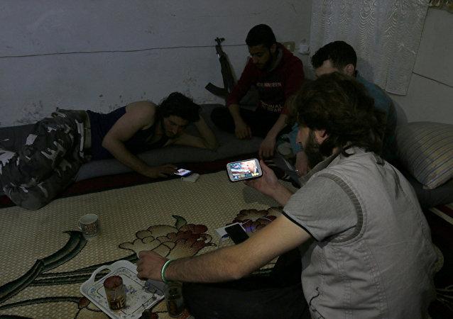 Islamiści z grupy Harakat Nour al-Din al-Zenki oglądają na smartfonie wiadomości po ogłoszeniu wyniku wyborów prezydenckich w USA, Aleppo, 9 listopada 2016