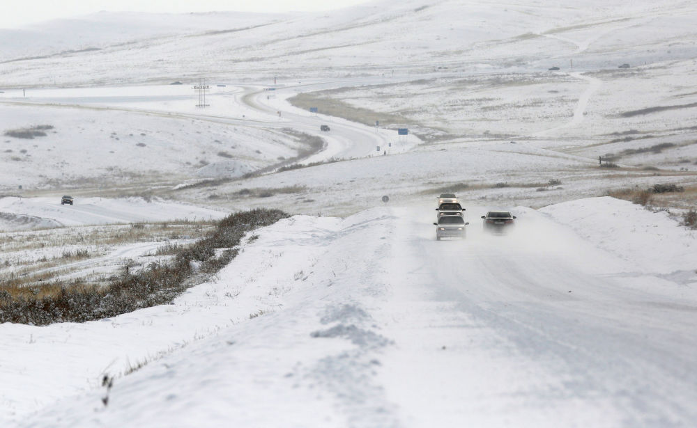 Samochody na zaśnieżonej drodze w okolicach miasta Kyzyl w Tuwie