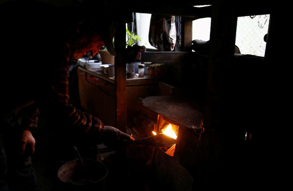 Węglarz pali w piecu na terenie wypału drewna, w lesie nieopodal Bieszczad w Polsce